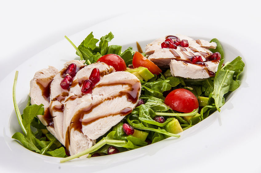 Salad with chicken with pomegranate sauce on a white background